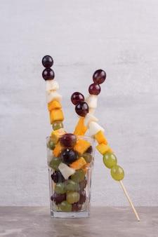 Um copo de frutas na mesa branca.