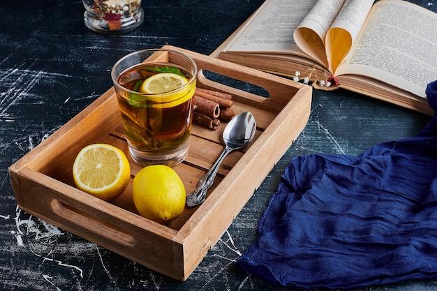 Um copo de glintwine com limões em uma bandeja de madeira.