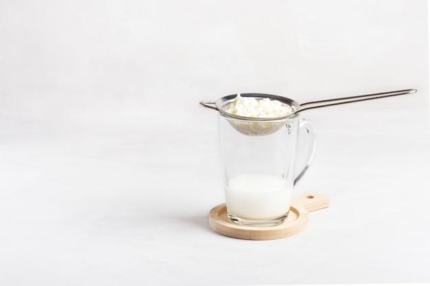Um copo de kefir caseiro com grãos de kefir fica em um fundo branco