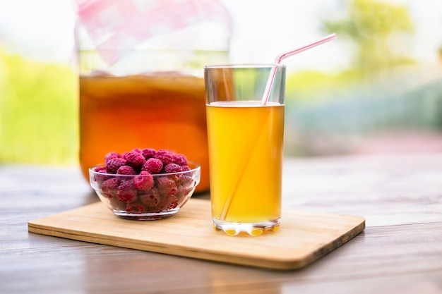Um copo de kombucha e no fundo do jardim de verão e do céu