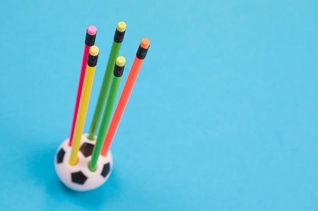 Um copo de lápis de forma de bola de futebol redondo com cinco lápis coloridos nele na superfície azul isolado