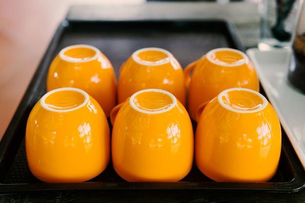 Um copo de laranja é colocado em uma bandeja de madeira em cima da mesa.