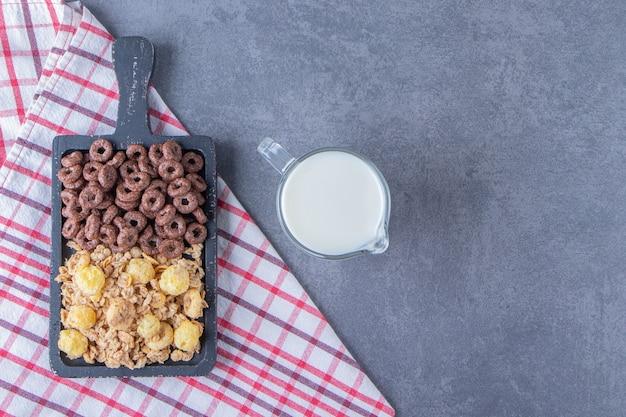 Um copo de leite ao lado de anéis de milho e flocos de milho em uma placa sobre o pano de prato, na mesa de mármore.