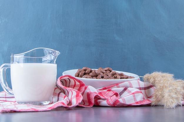 Um copo de leite ao lado de anéis de milho em uma tigela de vidro ao lado de capim-dos-pampas no pano de prato, na mesa de mármore.