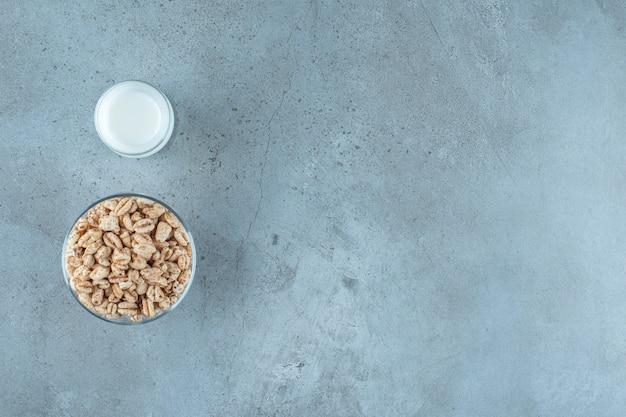 Um copo de leite ao lado de flocos de milho em um pedestal de vidro, no fundo de mármore.