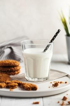 Um copo de leite, biscoitos, uma jarra de leite em uma superfície clara
