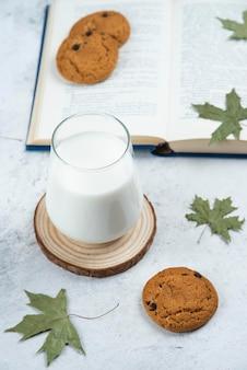 Um copo de leite com biscoitos de chocolate em uma placa de madeira.