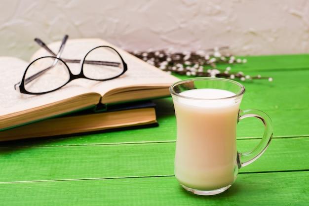 Um copo de leite com livros e copos em uma mesa de madeira verde