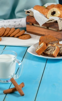 Um copo de leite com paus de canela e um biscoito em uma mesa de madeira azul.