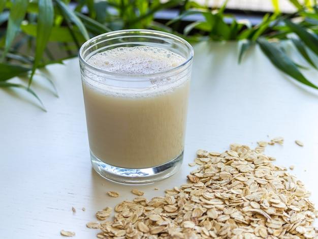 Um copo de leite de aveia com aveia ao redor