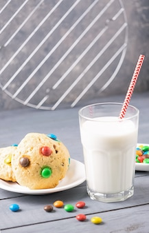 Um copo de leite e biscoitos decorados com balas de gelatina colorida