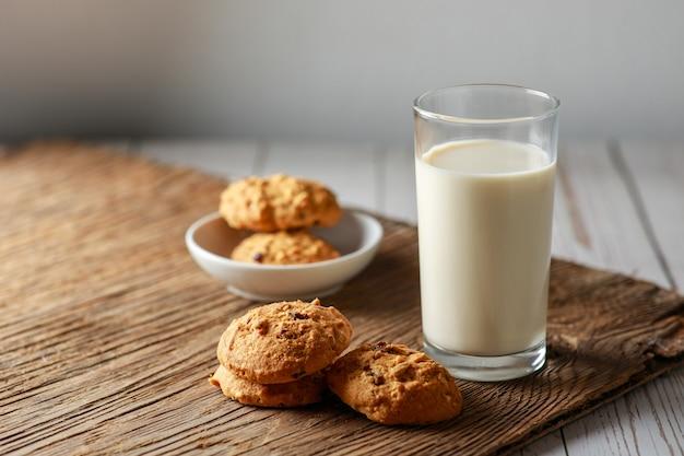 Um copo de leite fresco com biscoitos de chocolate na superfície de madeira branca