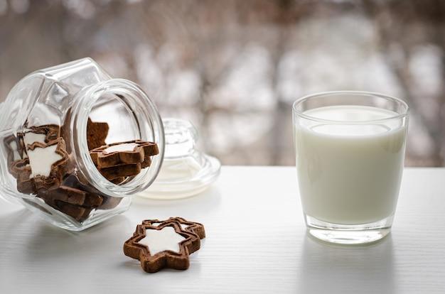 Um copo de leite orgânico fresco com biscoitos em forma de estrela na vista da janela de inverno