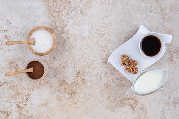 Um copo de leite, pequenas tigelas de açúcar e pó de café moído, uma xícara de café e amendoim glaceado