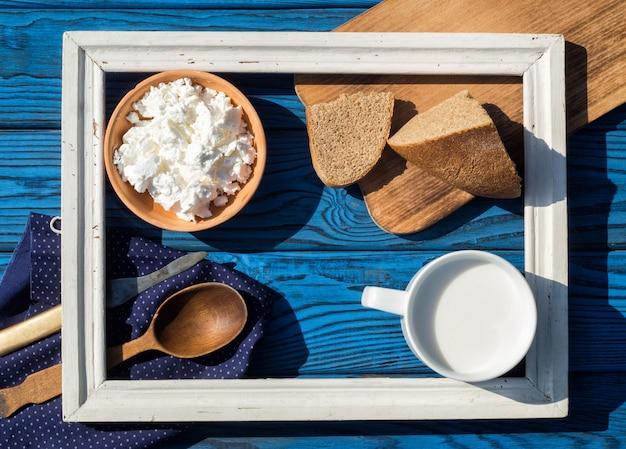 Um copo de leite, queijo cottage e pão dentro de uma moldura branca em uma mesa de placas azuis. vista do topo