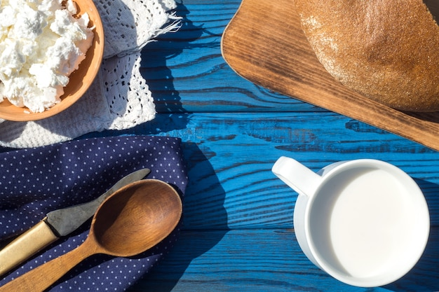 Um copo de leite, queijo cottage e pão sobre uma mesa de placas azuis. vista do topo