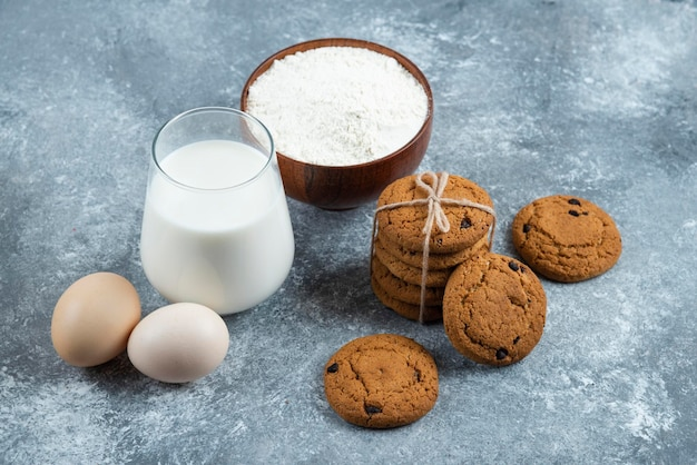 Um copo de leite quente com deliciosos biscoitos sobre uma mesa cinza.