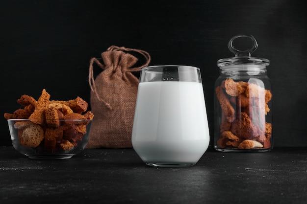 Um copo de leite servido com bolachas e frutos secos.