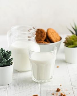 Um copo de leite, um jarro de leite, biscoitos sobre um fundo claro