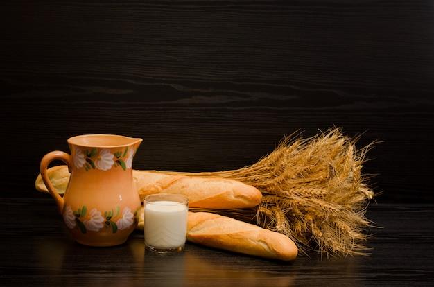 Um copo de leite, uma jarra e maço de pães