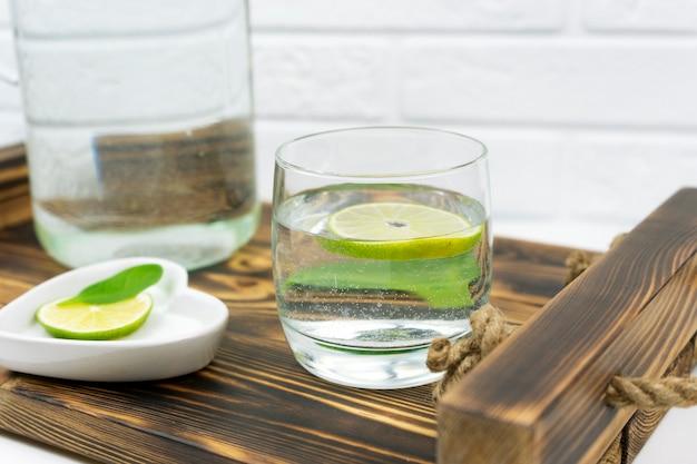 Um copo de limonada caseira está em uma bandeja de madeira