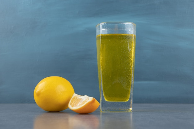 Um copo de limonada com cubos de gelo e limão cortado