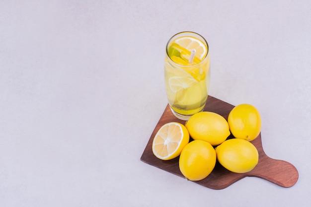 Um copo de limonada com limões em uma travessa de madeira