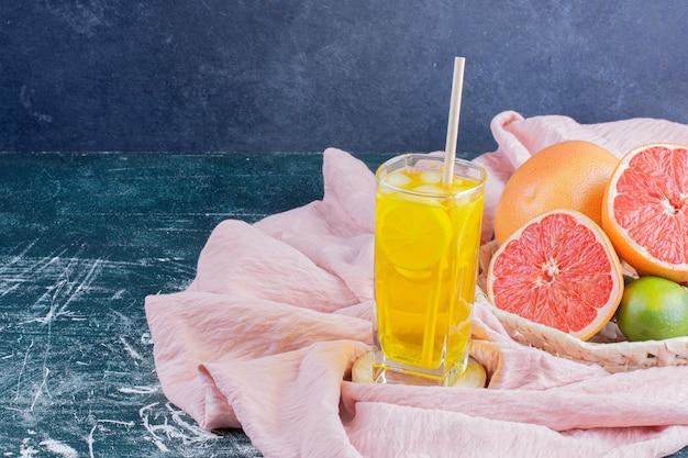 Um copo de limonada com rodelas de limão e toranjas na superfície de mármore.