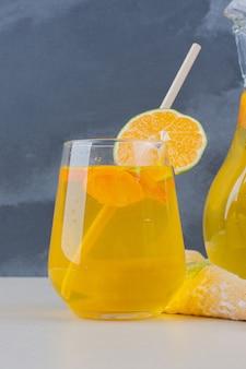Um copo de limonada com rodelas de limão na mesa branca.