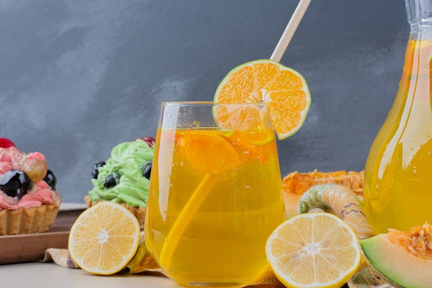 Um copo de limonada e cupcakes cremosos na mesa.