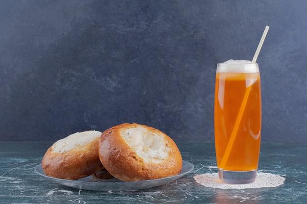 Um copo de limonada e pãezinhos de queijo na mesa de mármore.