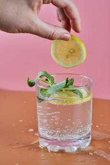 Um copo de limonada refrescante gelada na superfície rosa e uma mulher segurando uma rodela de limão