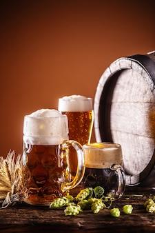 Um copo de litro cheio de chope ao lado de duas cervejas menores em frente a um barril de madeira como decoração de cevada e lúpulo.