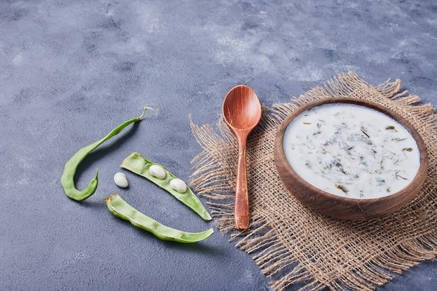 Um copo de madeira de sopa de iogurte com feijão verde.
