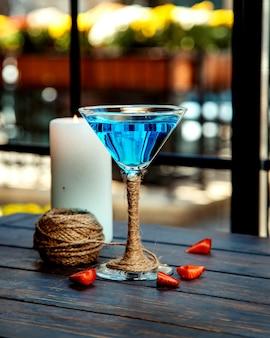Um copo de martini de lagoa azul decorado com juta