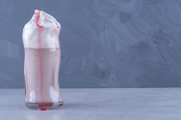 Um copo de milkshake com creme de morango na mesa de mármore.
