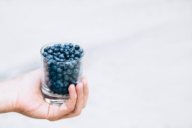 Um copo de mirtilos na mão