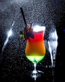Um copo de ombre cocktail com suco de verde e laranja em fundo escuro com luz