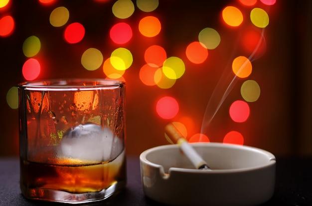 Um copo de on the rock com cigarro no cinzeiro