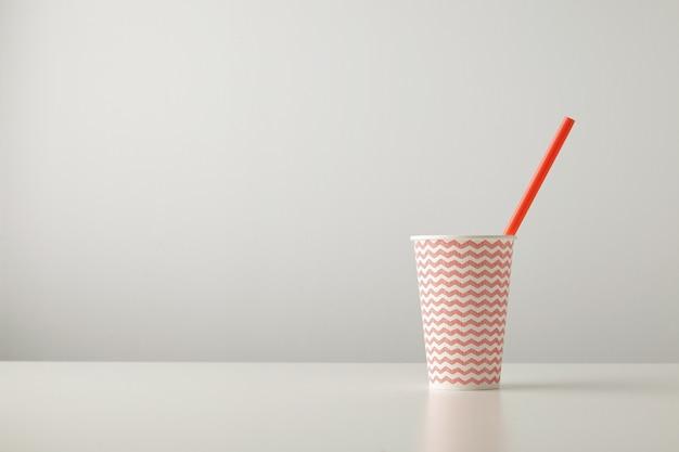 Um copo de papel decorado com um padrão de linha vermelha e com um canudo dentro isolado na mesa branca
