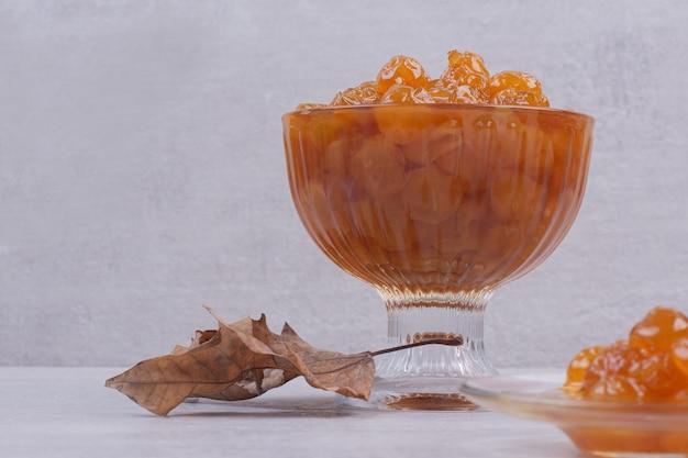 Um copo de prato com geléia e folhas na mesa branca.