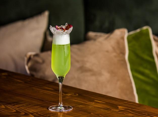 Um copo de prosecco verde com frutas vermelhas por cima
