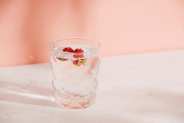 Um copo de refrigerante fresco com framboesas