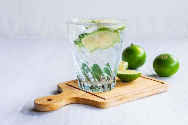 Um copo de refrigerante, limão e limão em cima da mesa