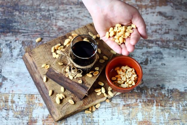 Um copo de refrigerante preto e amendoim. amendoins salgados em um copo com coca-cola. comida americana.