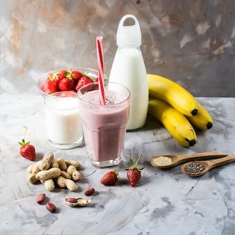 Um copo de smoothie de morango e banana entre os ingredientes para a sua preparação