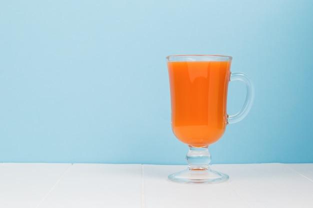 Um copo de smoothies em uma mesa branca sobre um fundo azul.