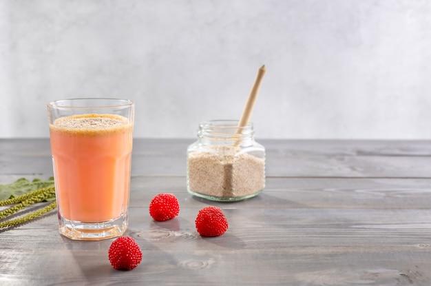 Um copo de smoothies feitos de bagas de rubus illecebrosus e leite de coco com cascas de sementes de psyllium