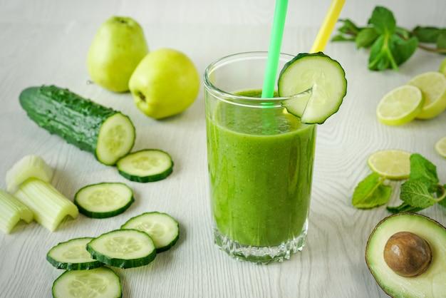 Um copo de smoothies vegetais verdes sobre um fundo branco de madeira