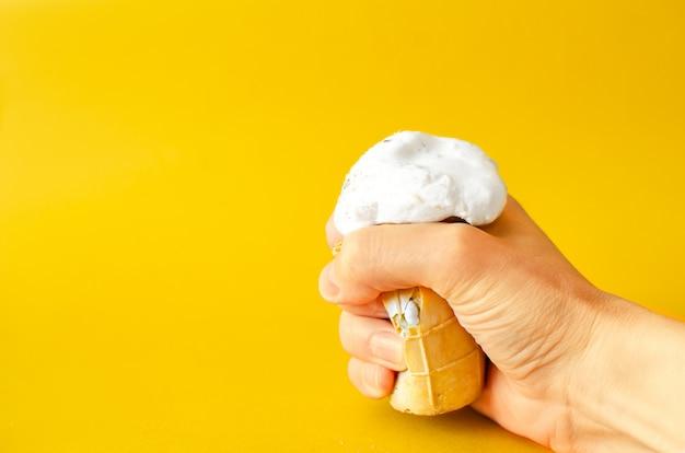Um copo de sorvete derrete na mão em um amarelo.